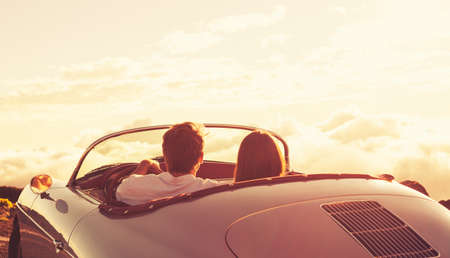 libertad: Romántica pareja joven y atractiva de ver el atardecer en Classic Vintage Sports Car Foto de archivo