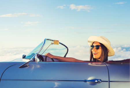 Счастливый молодая женщина за рулем в Классический ретро спортивный автомобиль Фото со стока