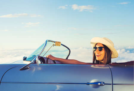 journeys: Happy Young Woman Driving in Classic Vintage Sports Car Stock Photo