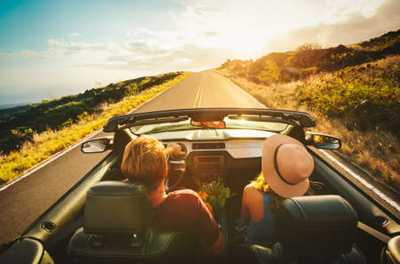two men: Happy Young Couple Driving Along Country Road in Convertible at Sunset
