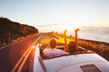 reizen: Gelukkig Paar Rijden op de Landweg in de Zonsondergang in de Classic Vintage Car Sport