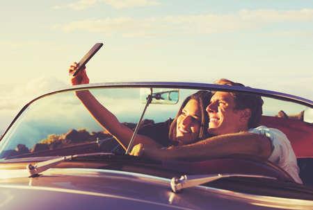 Coppia giovane romantico Facendo una Selfie in Classic Vintage Sports Car al tramonto