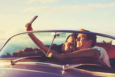 classic car: Romantic Young Couple Taking a Selfie in Classic Vintage Sports Car at Sunset Stock Photo