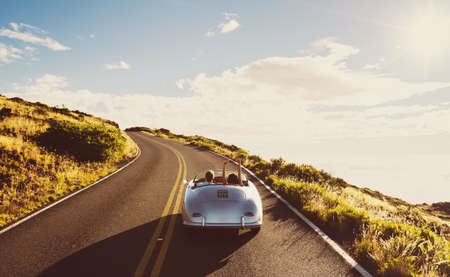 Pares felizes que conduzem na estrada secundária no Carro de esportes clássico do vintage