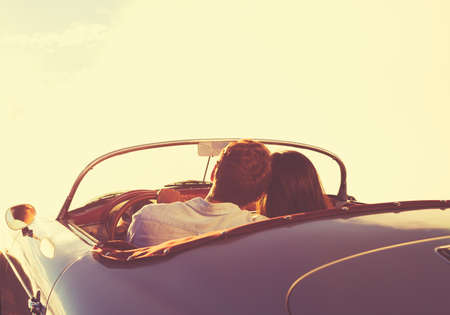 vintage: Romantic Young Attractive Couple Watching the Sunset in Classic Vintage Sports Car