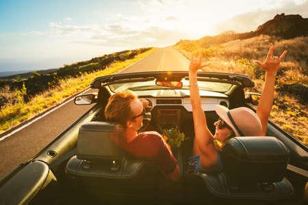 Gelukkig Jong Onbezorgd Paar rijden langs Landweg in Convertible bij zonsondergang
