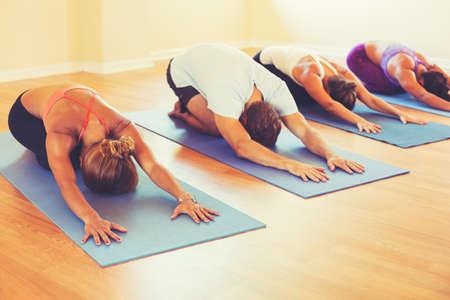 clases: Clase de yoga, Grupo de personas que se relaja y hacer yoga. Childs Pose. Bienestar y estilo de vida saludable. Foto de archivo