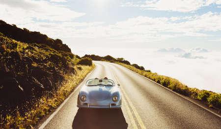 幸せなカップルの古典的なビンテージ スポーツ車で田舎道を走行