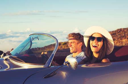 Счастливая молодая пара в Классический ретро спортивный автомобиль на закате
