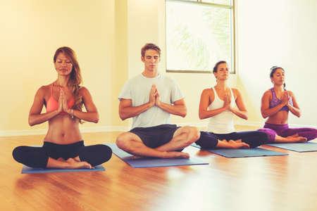 Grupo de pessoas que relaxa e meditando na classe da ioga. Bem-estar e estilo de vida saudável.