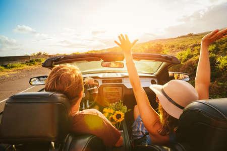 幸せな若い屈託のないカップル夕暮れコンバーチブルの田舎道に沿って運転