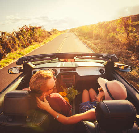 Счастливый молодая пара езды по проселочной дороге в кабриолете на закате