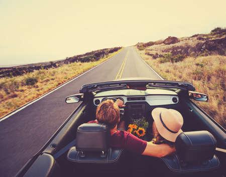 幸せな若いカップル夕暮れコンバーチブルの田舎道に沿って運転 写真素材