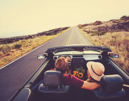 Feliz Pareja Joven Conducción a lo largo la carretera nacional en el convertible en el Sunset Foto de archivo - 44181461