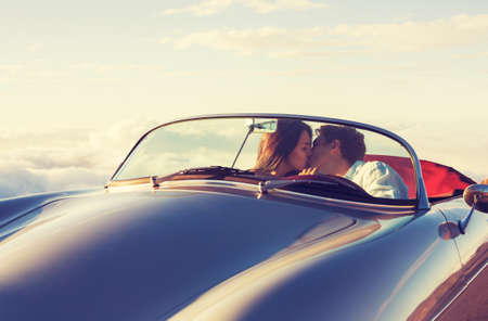 novios besandose: Romantic Young Attractive Couple Watching the Sunset and Kissing in Classic Vintage Sports Car Foto de archivo