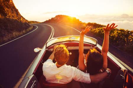 путешествие: Счастливая пара Езда на проселочной дороге в Закат в классическом Vintage спортивный автомобиль Фото со стока