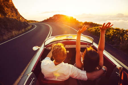 parejas jovenes: Pareja feliz de conducci�n en la carretera nacional en el Atardecer en Classic Vintage Sports Car Foto de archivo