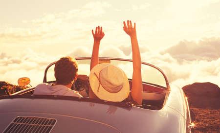 Вождение в закат. Счастливый молодая пара наслаждаясь закатом в классическом Vintage спортивный автомобиль Фото со стока