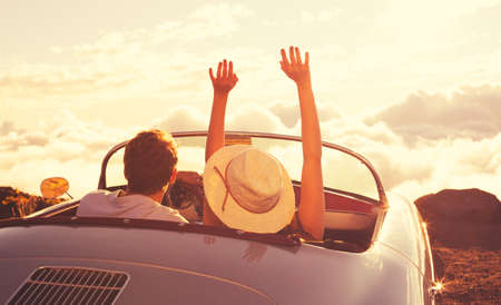 夕日に運転。クラシックなビンテージ スポーツカーで夕日を楽しむ幸せな若いカップル