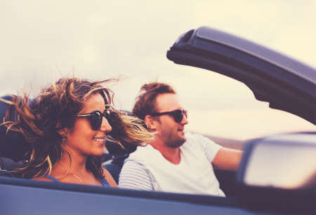 Happy Young Couple Driving Along Country Road in Convertible at Sunset Stock Photo - 44181286