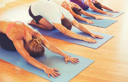 Classe di yoga, Gruppo di persone rilassante e fare yoga. Childs Pose. Benessere e Salute. Archivio Fotografico
