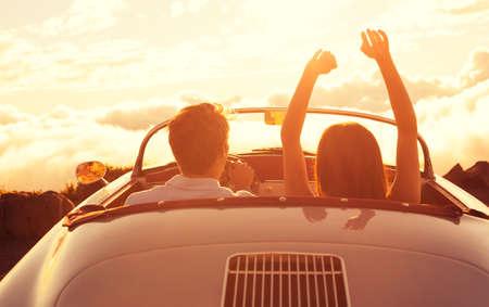 석양 속으로 운전. 클래식 빈티지 스포츠카의 일몰을 즐기는 행복 한 젊은 커플