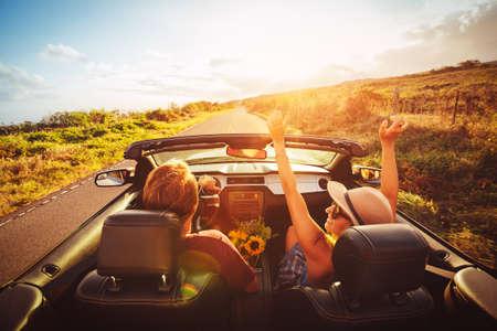 Gelukkig Jong Onbezorgd Paar rijden langs Landweg in Convertible bij zonsondergang Stockfoto