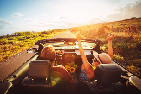 carefree: Happy Young Carefree Couple Driving Along Country Road in Convertible at Sunset