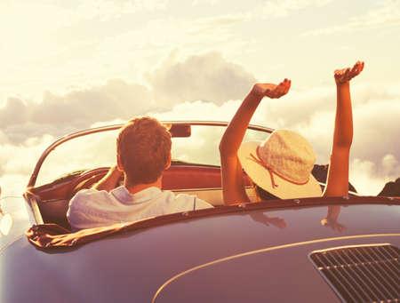 Conduire dans le Sunset. Heureux jeune couple le coucher du Soleil dans vintage classique de voiture de sport. Banque d'images - 44181334