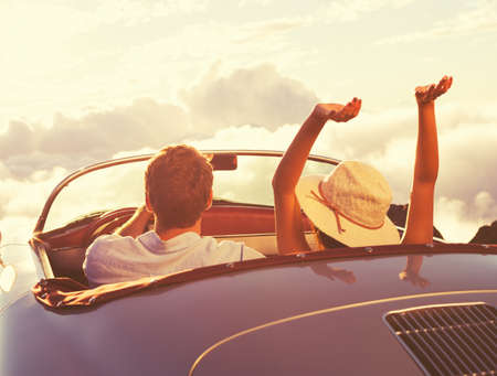 Driving into the Sunset. Happy Young Couple Enjoying the Sunset in Classic Vintage Sports Car.