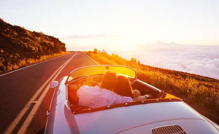manejando: Pareja Romántica Conducir en la puesta del sol en Classic Vintage Sports Car Foto de archivo