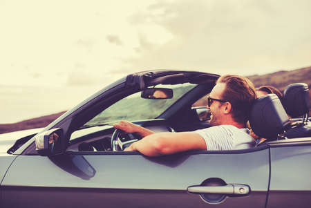 Happy Young Couple Driving Along Country Road in Convertible at Sunset Stock Photo - 44180761