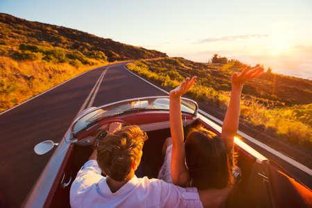 Condução no por do sol. Casal Jovem românticos que apreciam a Sunset Drive em Carro de esportes clássico do vintage