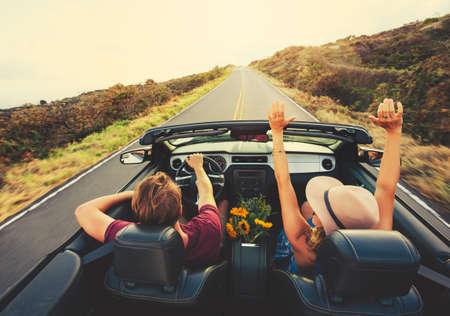 persona alegre: Feliz joven despreocupado Pareja Conducci�n a lo largo la carretera nacional en el convertible en el Sunset