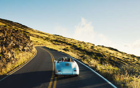 open road: Happy Couple Driving on Country Road in Classic Vintage Sports Car