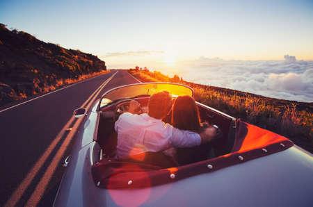 석양 속으로 운전. 클래식 빈티지 스포츠카에 일몰 드라이브를 즐기는 로맨틱 젊은 부부