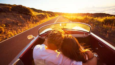 Вождение в закат. Романтический молодая пара наслаждается Закат Drive в классическом Vintage спортивный автомобиль
