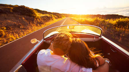happy couple: Driving into the Sunset. Romantic Young Couple Enjoying Sunset Drive in Classic Vintage Sports Car Stock Photo