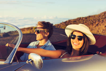 Happy Young Couple in Classic Vintage Sports Car at Sunset photo