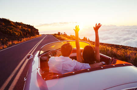 arms raised: Driving into the Sunset. Romantic Young Couple Enjoying Sunset Drive in Classic Vintage Sports Car Stock Photo