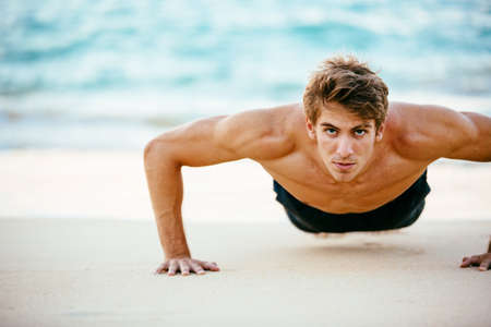 push: Fitness man doing push-ups on the beach. Male athlete exercising outdoors. Sports and active lifestyle.