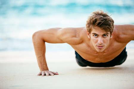 해변에서 팔 굽혀 펴기를하고 휘트니스 남자. 야외 운동 남자 선수. 스포츠 및 활동적인 라이프 스타일.