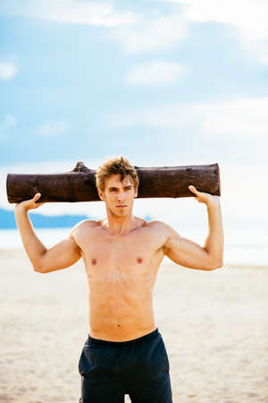 male athlete: CrossFit beach workout. Male athlete exercising outdoors at the beach with tree log. Fitness and healthy lifestyle.