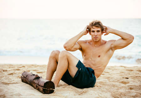 muscular body: Attractive male athlete doing sit ups and abdominal workout. Exercising outdoors at the beach.