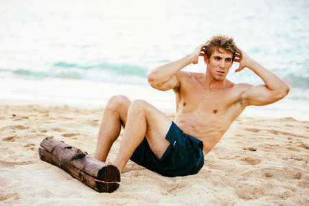 male athlete: Attractive male athlete doing sit ups and abdominal workout. Exercising outdoors at the beach.