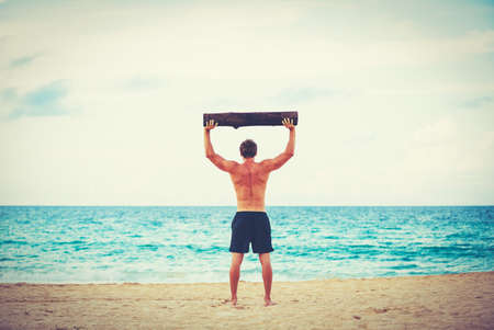 CrossFit beach workout. Male athlete exercising outdoors at the beach with tree log. Fitness and healthy lifestyle.