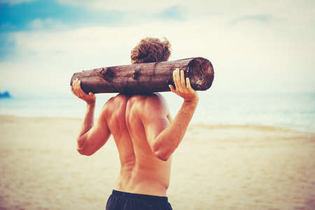 manly man: CrossFit beach workout. Male athlete exercising outdoors at the beach with tree log. Fitness and healthy lifestyle.