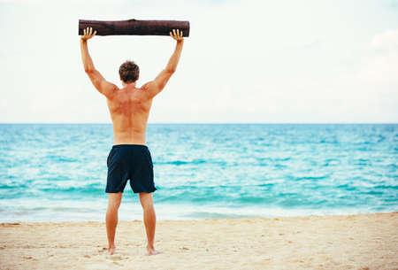 CrossFit strand workout. Mannelijke atleet in openlucht uitoefent op het strand met boom log. Fitness en een gezonde levensstijl.