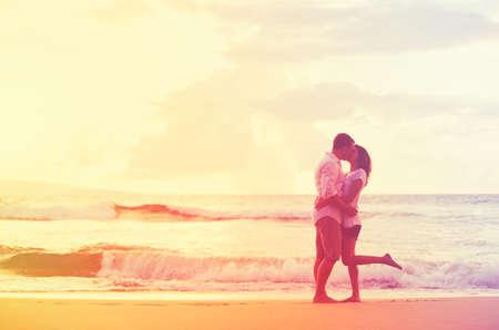 personas abrazadas: Pareja Romántica Feliz besan en la playa al atardecer