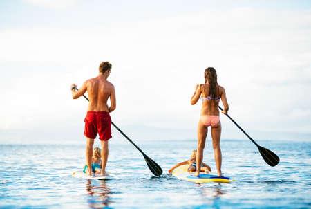 가족 재미 아름 다운 화창한 아침에 바다에서 함께 패들링 일어 서서 데